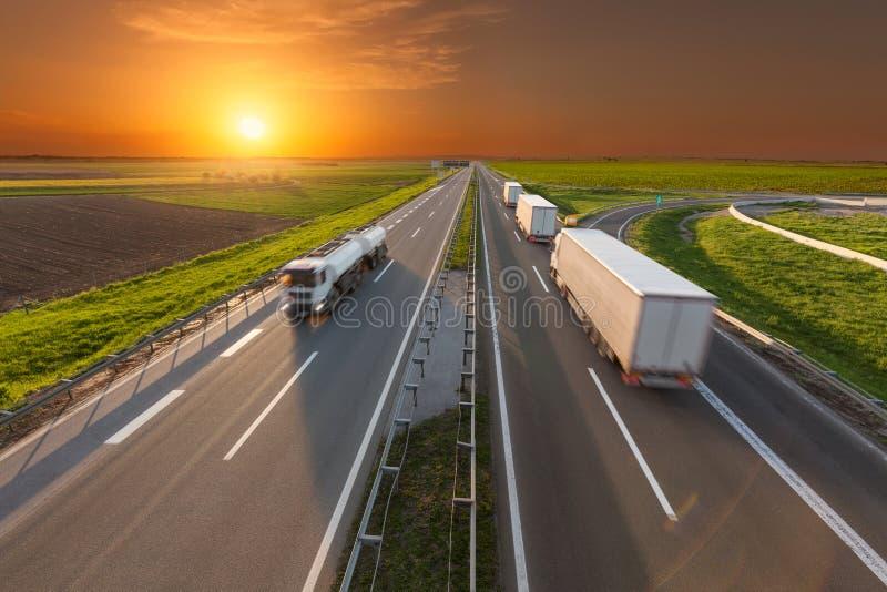 Camión en la falta de definición de movimiento en la autopista sin peaje en la puesta del sol imagen de archivo