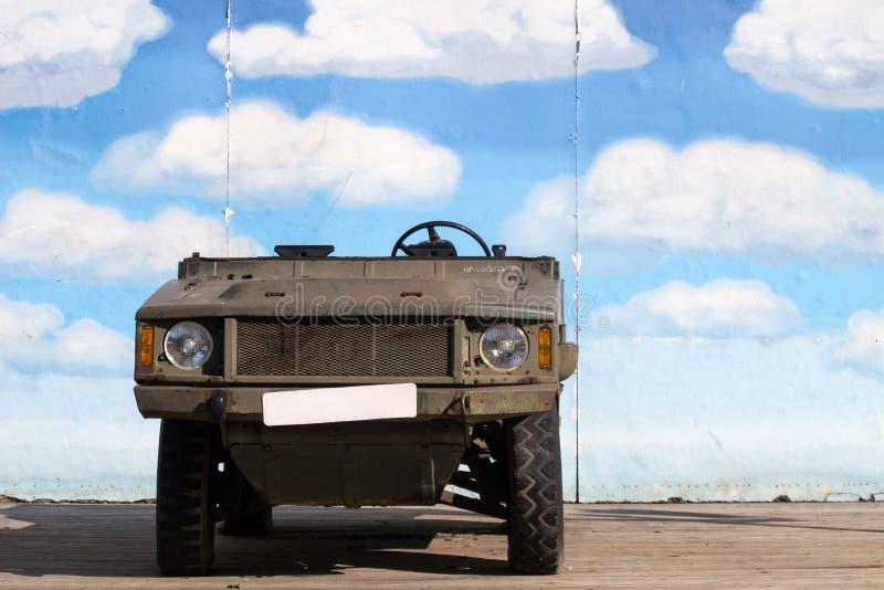 Camión militar viejo Jeep Stand delante del cielo azul Demo Wall imagen de archivo libre de regalías