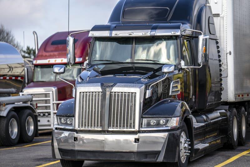 Camión moderno del aparejo grande negro semi con semi la situación del remolque en la parada de camiones con otros semi camiones imagen de archivo libre de regalías