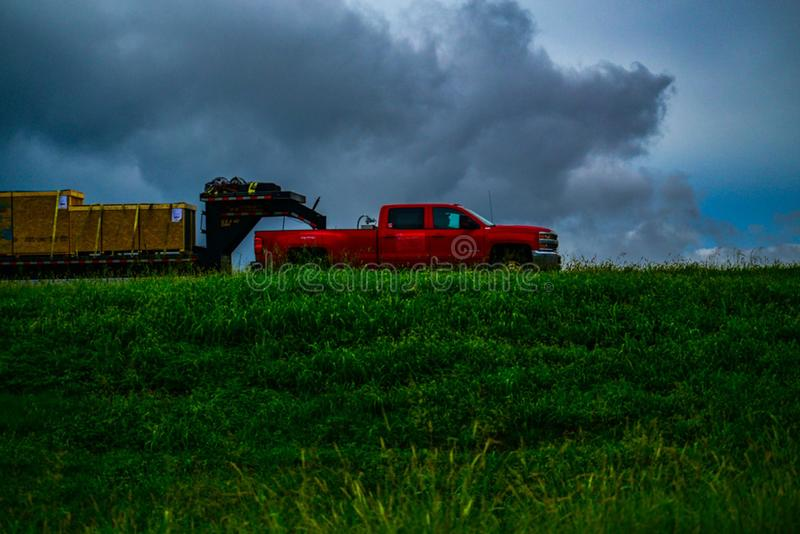 Camión rojo que remolca el envío contra las nubes grises fotografía de archivo