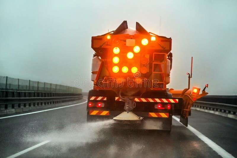 Cami?n del gritter del mantenimiento de la carretera que separa la sal de icing en el camino imagen de archivo