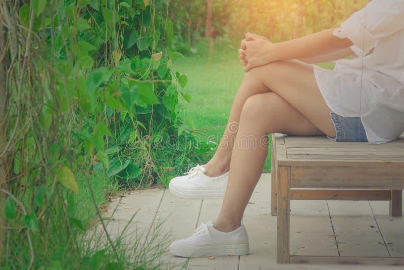 Camicia bianca di usura di donna e breve tralicco, lei che si rilassa sulla sedia di legno al giardino all'aperto circondato fotografia stock