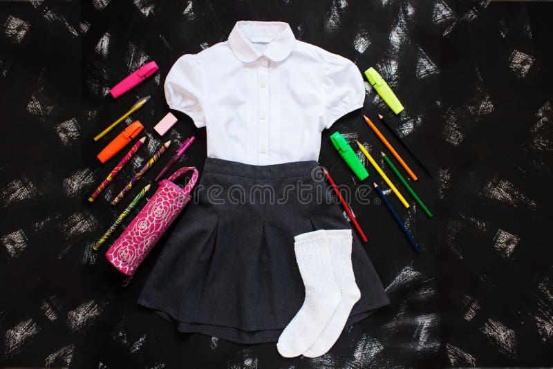 Camicia bianca, gonna grigia e rifornimenti della cancelleria su fondo nero Il primo settembre, nuovo anno scolastico immagini stock