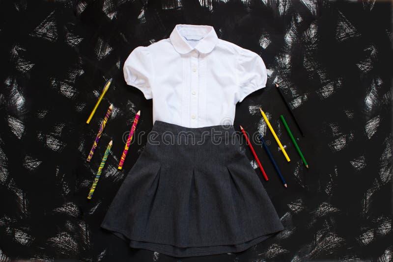 Camicia bianca, gonna grigia e rifornimenti della cancelleria su fondo nero Il primo settembre, nuovo anno scolastico immagini stock libere da diritti