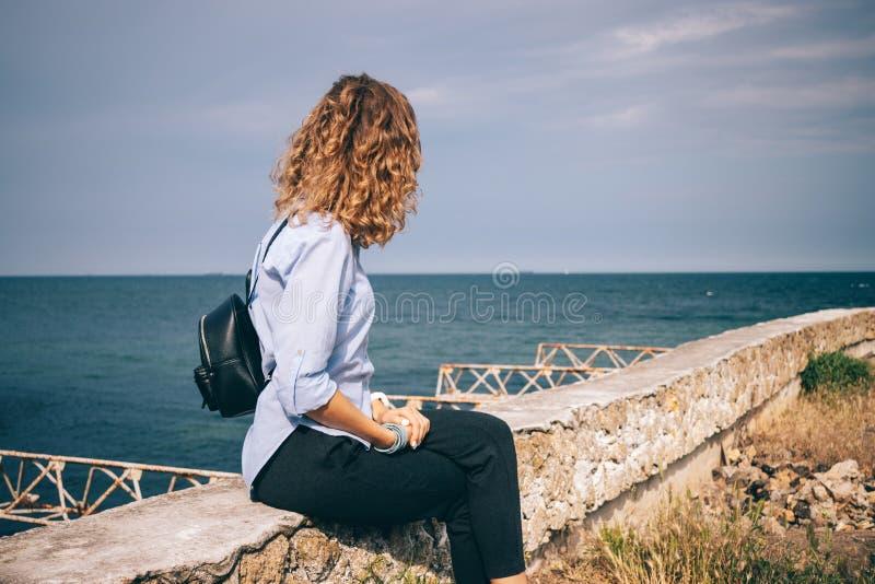 Camicia blu d'uso femminile di vista laterale, pantaloni neri e zaino fotografia stock