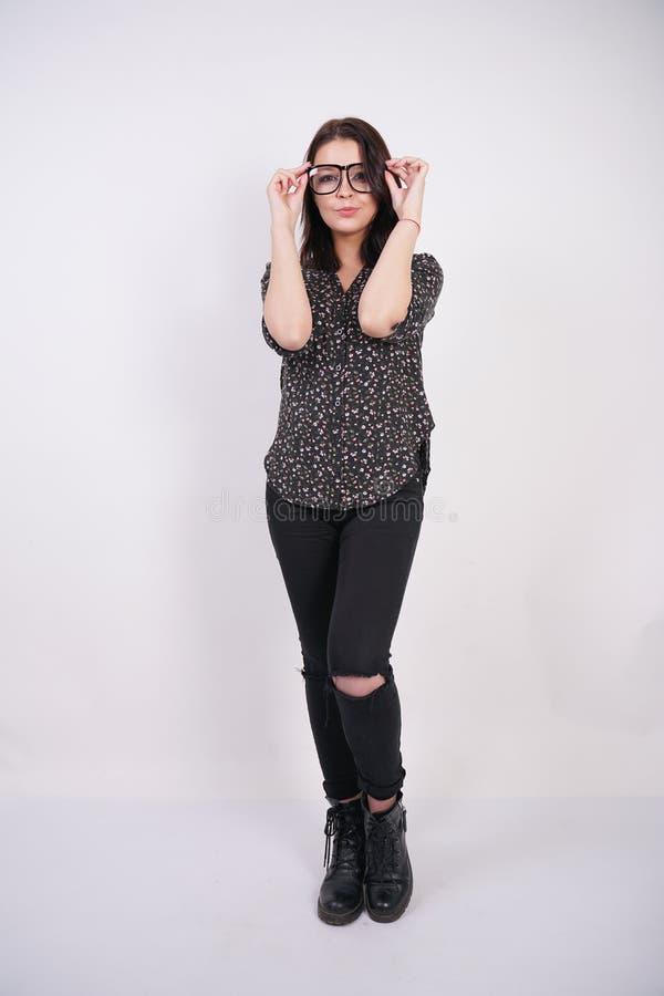 Camicia casuale d'uso di modo della ragazza teenager graziosa e jeans lacerati neri che posano con gli occhiali sul fondo bianco  fotografia stock libera da diritti