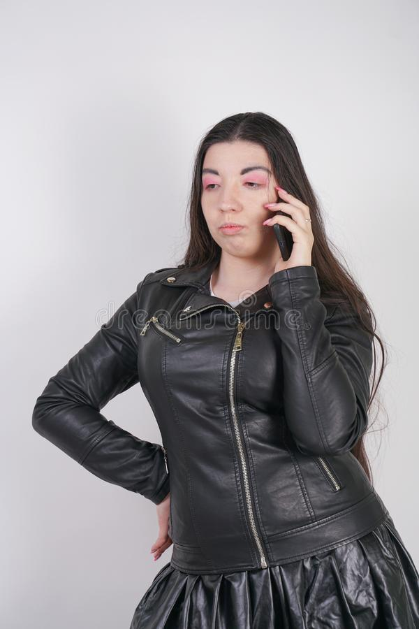 Camicia d'uso di anime della ragazza alternativa alla moda e gonna di cuoio con il rivestimento della roccia su fondo bianco immagine stock libera da diritti