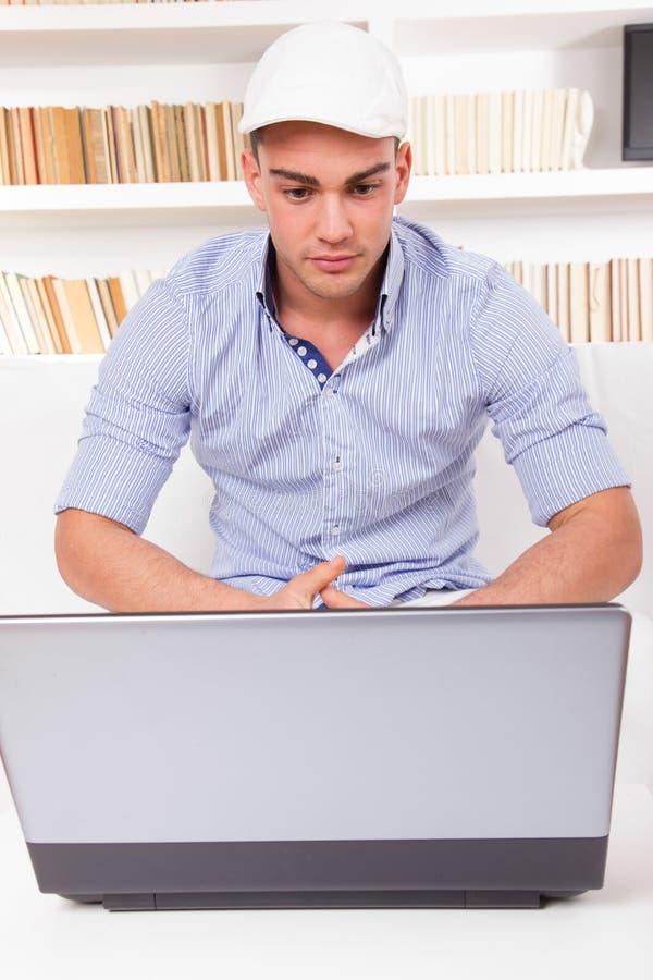 Camicia d'uso e cappuccio del giovane che esaminano il monitor del computer fotografie stock libere da diritti