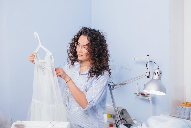 Camicia da notte di misurazione del sarto da donna nel luogo di lavoro fotografia stock