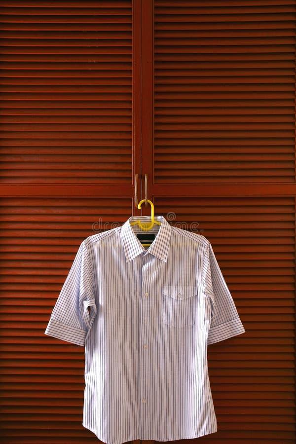 Camicia di polo che appende da una porta di gabinetto dei vestiti fotografia stock