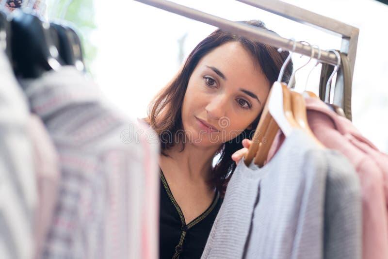 Camicia di ricerca femminile sui ganci in deposito fotografia stock