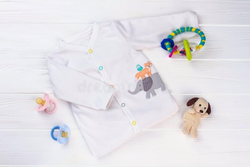 Camicia e giocattoli molli bianchi del bambino fotografia stock