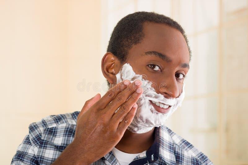 Camicia quadrata blu bianca d'uso del modello del giovane che si applica radendo schiuma sul fronte facendo uso delle mani, esami immagine stock