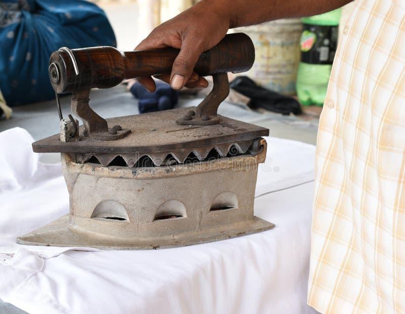 Camicia rivestente di ferro della mano dell'uomo indiano con ferro a base di carbone enorme immagini stock libere da diritti