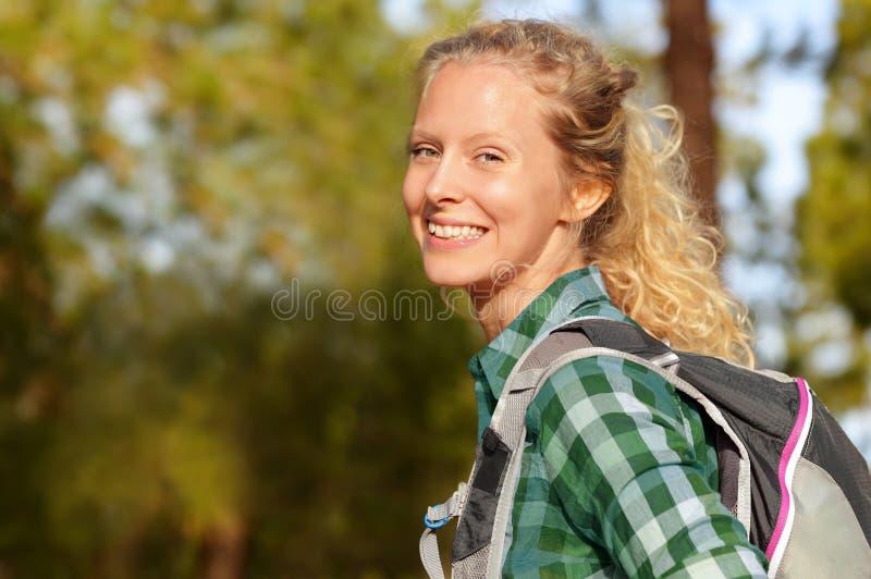 Caminando la sonrisa del retrato de la mujer feliz en muchacha femenina del caminante del bosque imagenes de archivo