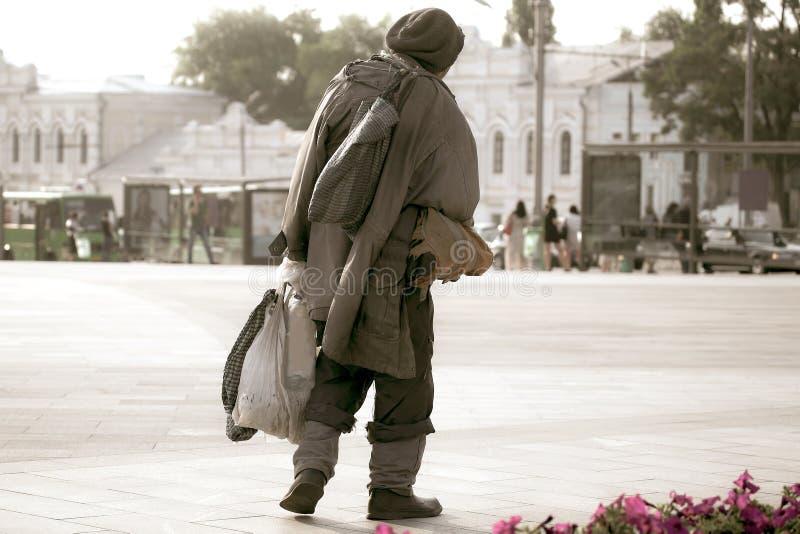 Caminando a través de la plaza a un hombre sin hogar fotos de archivo libres de regalías