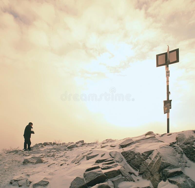 Caminante alto en negro en el pico del mundo Bramido anaranjado pesado de la niebla en valle fotos de archivo libres de regalías