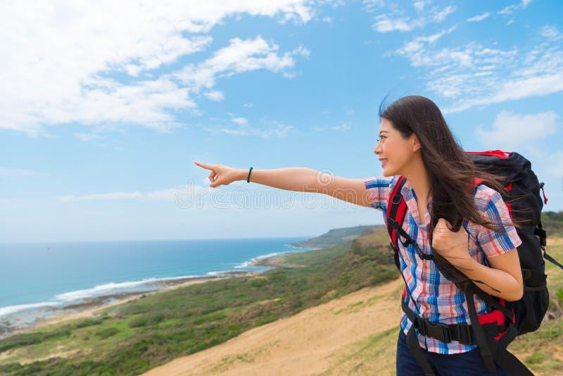 Caminante asiático que señala al copyspace limpio del cielo foto de archivo
