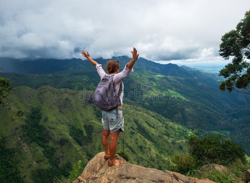 Caminante caucásico joven de la mujer con la mochila que se coloca encima de la montaña y que disfruta de la opinión del valle en fotografía de archivo