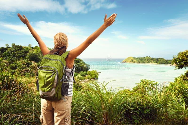 Caminante con la mochila que disfruta de la opinión del mar del top de una montaña fotografía de archivo libre de regalías
