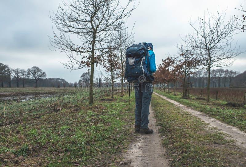 Caminante con la mochila que se coloca en el camino de tierra con las pistas del neumático imágenes de archivo libres de regalías