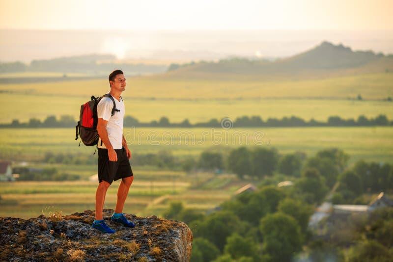 Caminante con la mochila que se coloca encima de una montaña imagen de archivo libre de regalías