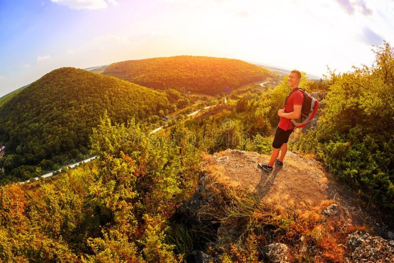 Caminante con la mochila que se coloca encima de una montaña fotografía de archivo libre de regalías