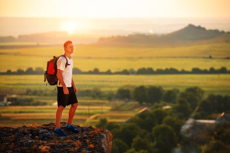 Caminante con la mochila que se coloca encima de una montaña fotografía de archivo