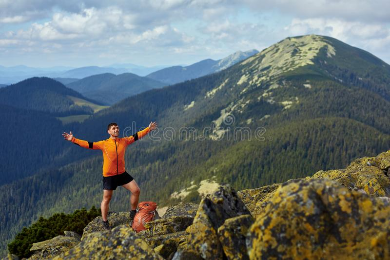 Caminante con la mochila que se coloca encima de una montaña con las manos aumentadas fotografía de archivo libre de regalías