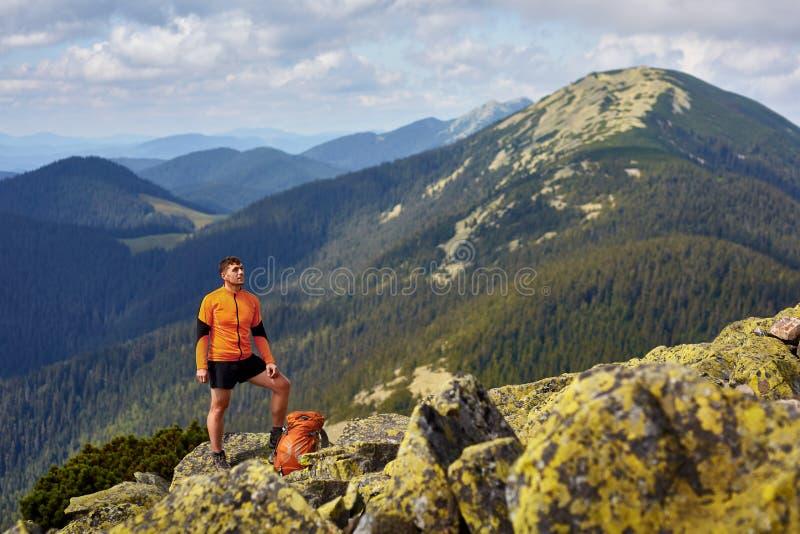 Caminante con la mochila que se coloca encima de una montaña con las manos aumentadas fotos de archivo libres de regalías