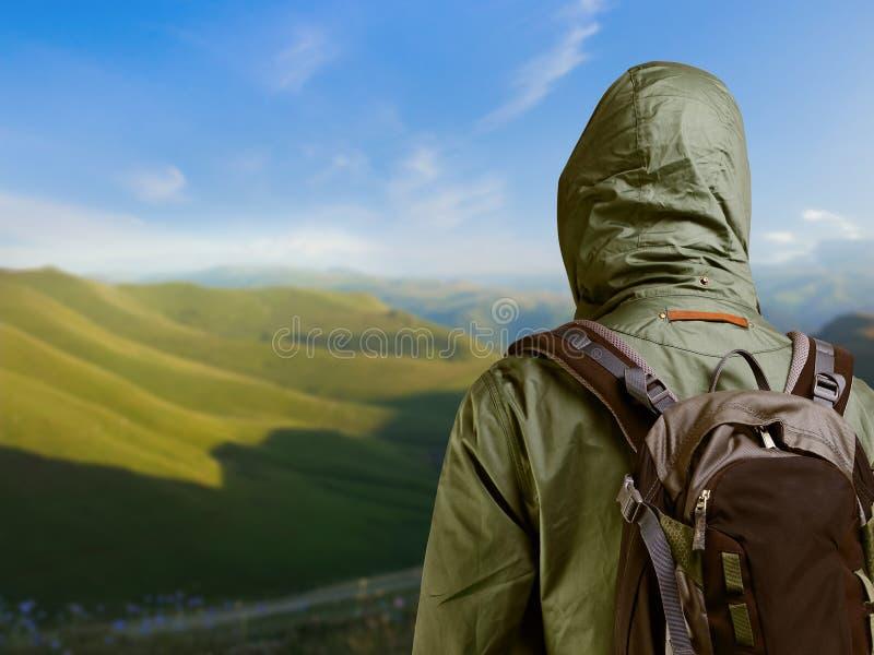 Caminante con la mochila que se coloca encima de una montaña y que disfruta de n fotografía de archivo