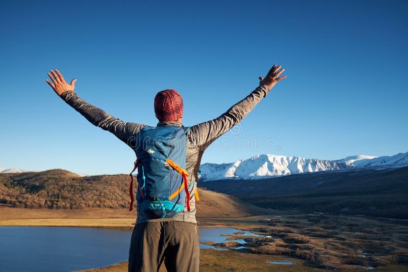 Caminante con la mochila que se coloca encima de una monta?a con las manos aumentadas fotografía de archivo libre de regalías