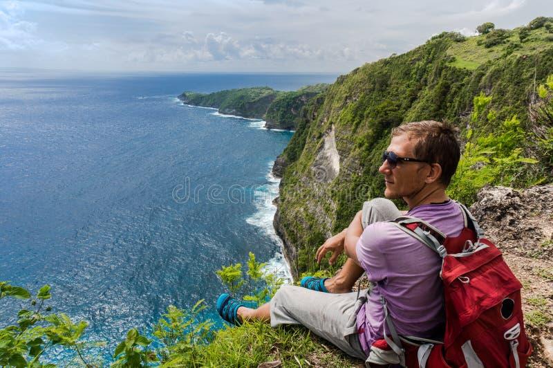 Caminante con la mochila que se sienta en el top de la montaña imagen de archivo libre de regalías