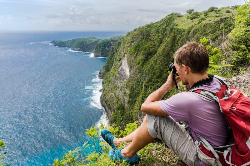 Caminante con la mochila que se sienta en el top de la montaña y que hace la foto imagenes de archivo