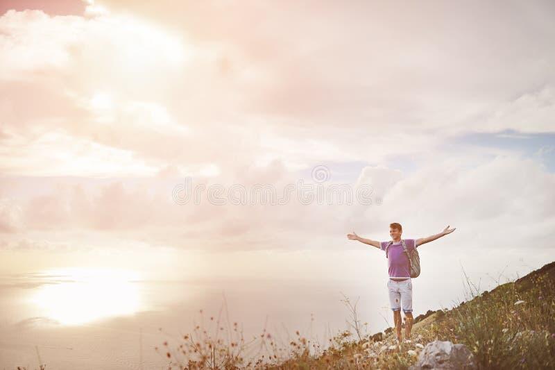 Caminante con los brazos abiertos de par en par encima de una montaña - concepto de la conquista de la libertad foto de archivo libre de regalías
