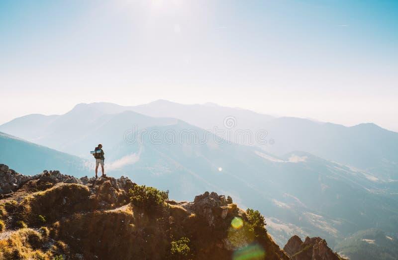Caminante de la montaña con estancia minúscula de la estatuilla de la mochila en pico de montaña imagen de archivo