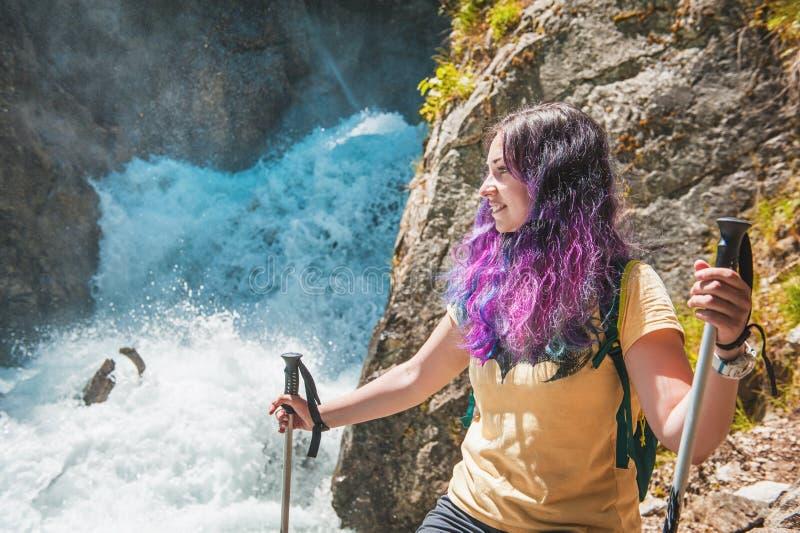 Caminante de la mujer con los palillos que miran en la cascada Concepto del turismo fotos de archivo libres de regalías