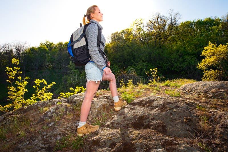 Caminante de la mujer con la mochila sobre fondo de la naturaleza Goce de la muchacha imagen de archivo libre de regalías