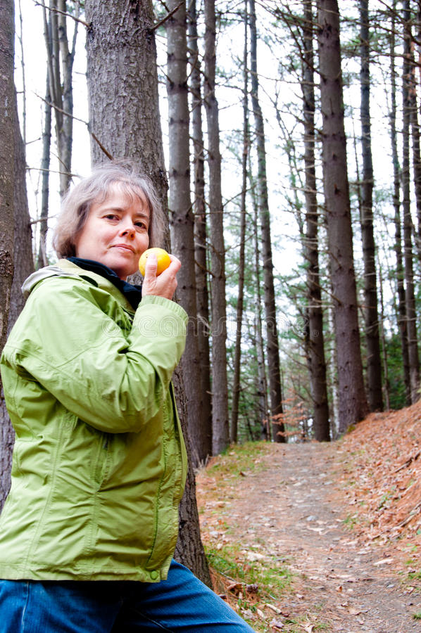 Caminante de la mujer con una manzana en las maderas fotografía de archivo
