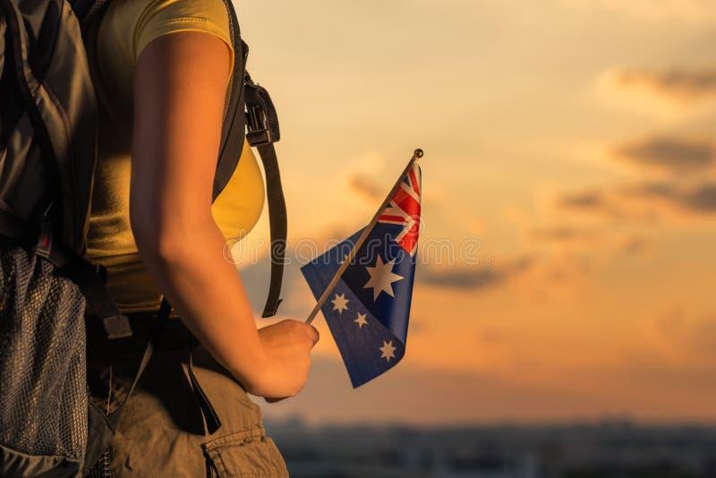 Caminante de la mujer en el top de la montaña en pantalones cortos y de una camiseta con una mochila y la bandera de Australia en imagen de archivo