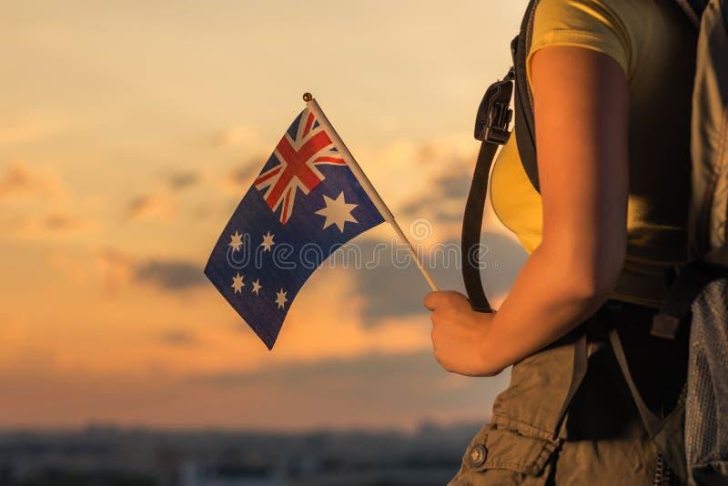 Caminante de la mujer en el top de la montaña en pantalones cortos y de una camiseta con una mochila y la bandera de Australia en fotos de archivo