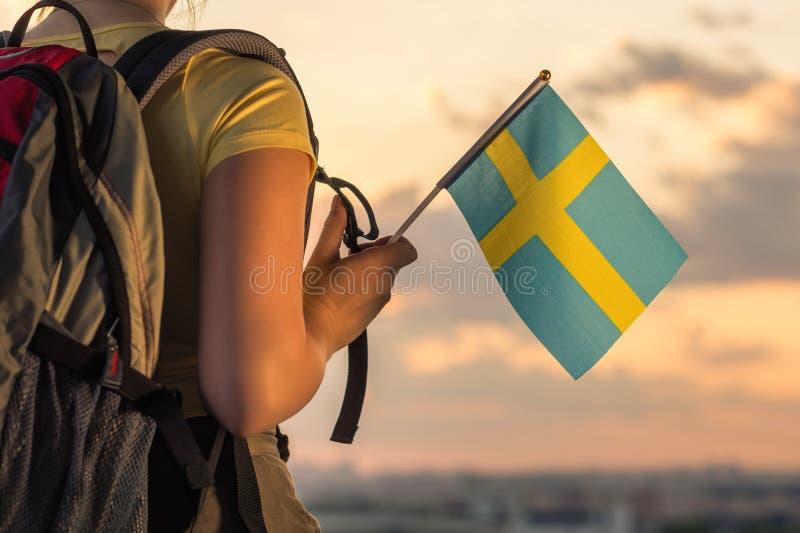 Caminante de la mujer en el top de la montaña en pantalones cortos y de una camiseta con una mochila y la bandera de Suecia en un imagen de archivo libre de regalías