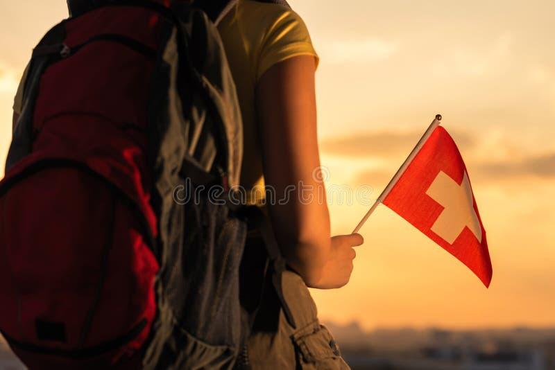 Caminante de la mujer en el top de la montaña en pantalones cortos y de una camiseta con una mochila y la bandera de Suiza en un  foto de archivo libre de regalías
