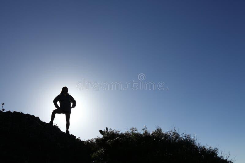 Caminante de la mujer en la silueta que se coloca en la montaña superior fotografía de archivo libre de regalías