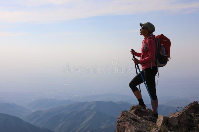 Caminante de la mujer joven con la mochila que se coloca encima de la montaña fotografía de archivo libre de regalías