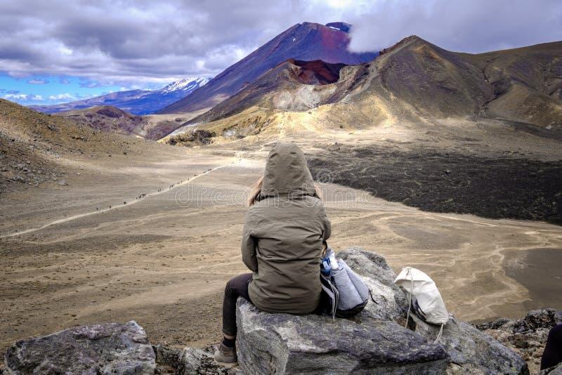 Caminante de la mujer que admira la opinión volcánica del paisaje de Tongariro, Nueva Zelanda foto de archivo