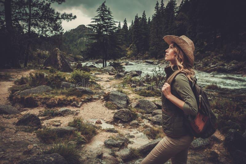 Caminante de la mujer que camina cerca del río salvaje de la montaña imagenes de archivo
