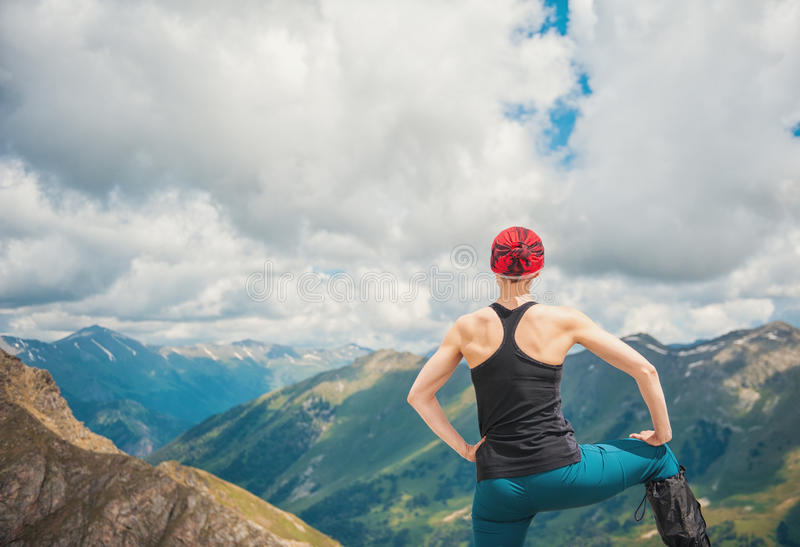 Caminante de la mujer que se coloca en el top de la montaña Actitud trasera fotos de archivo