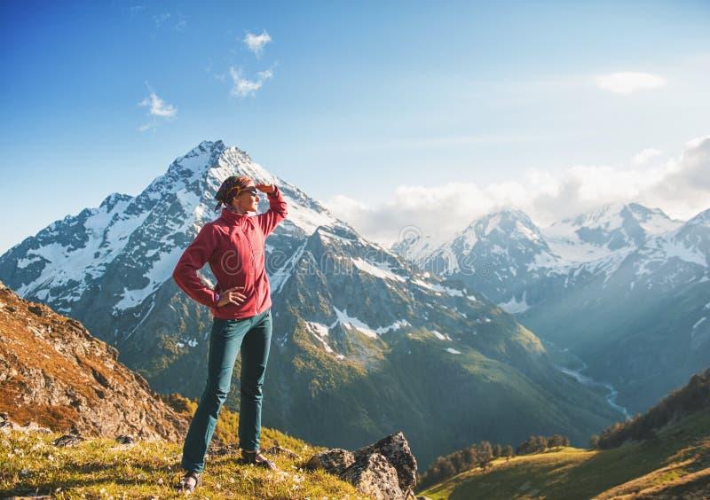 Caminante de la mujer que se coloca en el top de la montaña imagenes de archivo