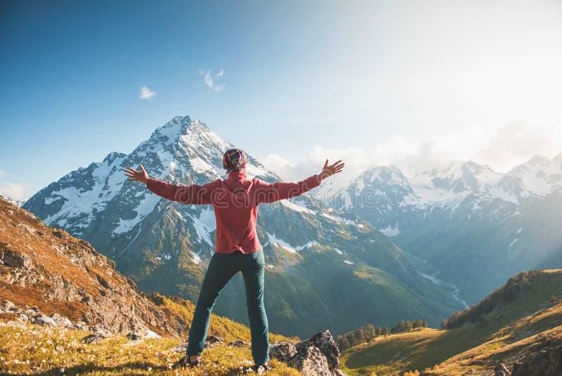 Caminante de la mujer que se coloca en el top de la montaña Actitud trasera fotos de archivo libres de regalías